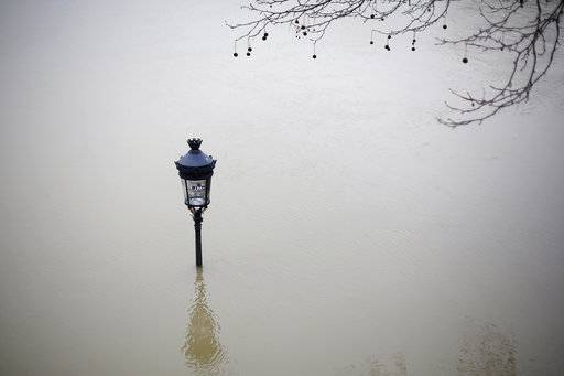 A flooded street lamp is pictured next to the river Seine in Paris, Saturday, Jan. 27, 2018. Floodwaters were nearing their peak in Paris on Saturday, with the rain-swollen Seine River engulfing scenic quays and threatening wine cellars and museum basements.