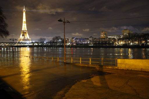 A flooded street lamp is pictured next to the river Seine in Paris in Paris, Saturday, Jan. 27, 2018. Floodwaters were nearing their peak in Paris on Saturday, with the rain-swollen Seine River engulfing scenic quays and threatening wine cellars and museum basements.