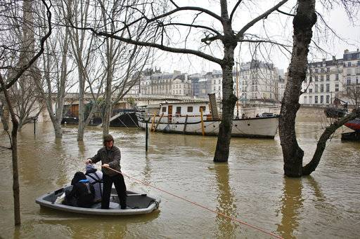 People use a dinghy boat to reach a barge on the river Seine in Paris, Saturday, Jan. 27, 2018. Floodwaters were nearing their peak in Paris on Saturday, with the rain-swollen Seine River engulfing scenic quays and threatening wine cellars and museum basements.