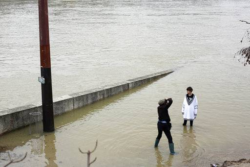 A photographer takes a picture of a model on the flooded banks of the river Seine in Paris, Saturday, Jan. 27, 2018. Floodwaters were nearing their peak in Paris on Saturday, with the rain-swollen Seine River engulfing scenic quays and threatening wine cellars and museum basements.