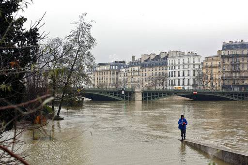 A woman walks along a low wall on the flooded banks of the river Seine in Paris, Saturday, Jan. 27, 2018. Floodwaters were nearing their peak in Paris on Saturday, with the rain-swollen Seine River engulfing scenic quays and threatening wine cellars and museum basements.