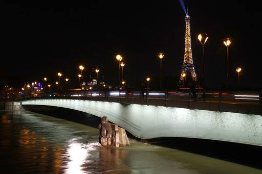 Water rushes past Alma bridge by the Zouave statue which is used as a measuring instrument during floods in Paris, Saturday, Jan. 27, 2018. Floodwaters were nearing their peak in Paris on Saturday, with the rain-swollen Seine River engulfing scenic quays and threatening wine cellars and museum basements.