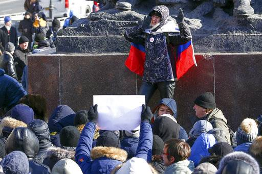 A demonstrator with a Russian national flag wrapped in his shoulders shouts slogans during a rally in Vladivostok, Russia, Sunday, Jan. 28, 2018. Opposition politician Alexey Navalny calls for nationwide protests following Russia's Central Election Commission's decision to ban his presidential candidacy.