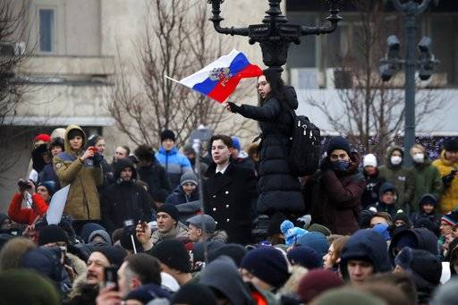 A protester waves a Russian flag during a rally at Pushkin square in Moscow, Sunday, Jan. 28, 2018. Opposition politician Alexey Navalny calls for nationwide protests following Russia's Central Election Commission's decision to ban his presidential candidacy.