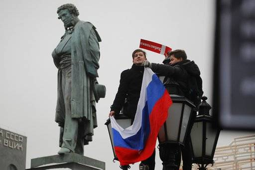 Young protesters hold a Russian flag during a rally at Pushkin square in Moscow, Sunday, Jan. 28, 2018. Opposition politician Alexey Navalny calls for nationwide protests following Russia's Central Election Commission's decision to ban his presidential candidacy.