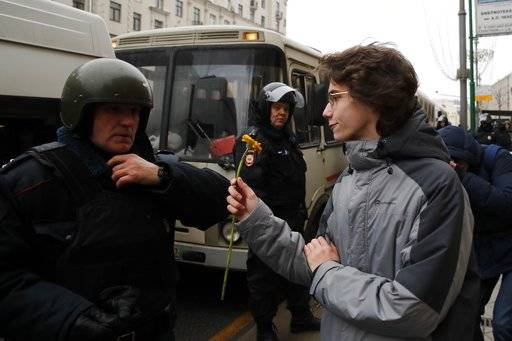 A protester offers a flower at a policeman during a rally in Moscow, Sunday, Jan. 28, 2018 against Russia's Central Election Commission's decision to ban the opposition leader Alexei Navalny presidential candidacy. Navalny has been arrested in Moscow as protests demonstrations called by him took place across the country.