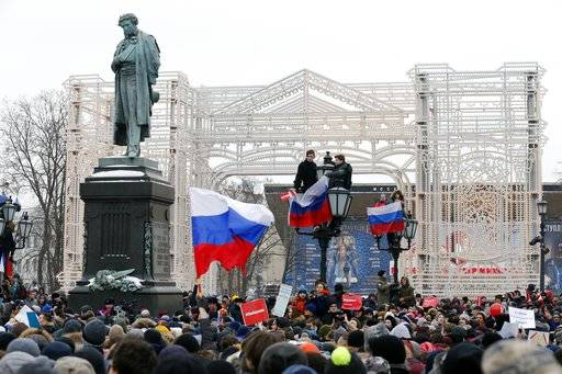 Protesters with Russian flags gather during a rally at Pushkin square in Moscow, Sunday, Jan. 28, 2018 against Russia's Central Election Commission's decision to ban the opposition leader Alexei Navalny presidential candidacy. Navalny has been arrested in Moscow as protests demonstrations called by him took place across the country.