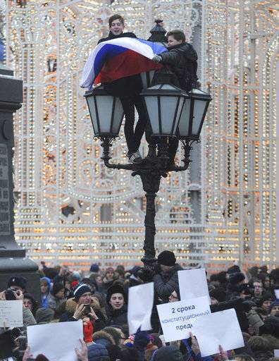 "Young protesters hold a Russian flag as others hold up banners, one at center reads: ""Two terms are the Constitutional Limit"", during a rally at Pushkin square in Moscow, Sunday, Jan. 28, 2018. Russian opposition leader Alexei Navalny has been arrested in Moscow as protest demonstrations called by him took place across the country. He has called on supporters to continue the demonstrations despite his arrest Sunday."