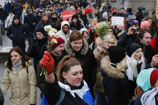 A protester holds up flowers during a rally in Moscow, Sunday, Jan. 28, 2018 against Russia's Central Election Commission's decision to ban the opposition leader Alexei Navalny presidential candidacy. Navalny has been arrested in Moscow as protests demonstrations called by him took place across the country.