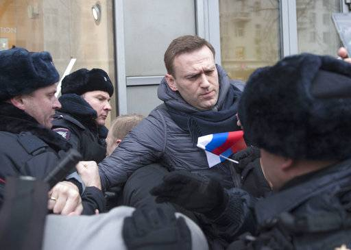 Russian opposition leader Alexei Navalny, centre, is detained by police officers in Moscow, Russia, Sunday, Jan. 28, 2018. Opposition politician Alexey Navalny calls for nationwide protests following Russia's Central Election Commission's decision to ban his presidential candidacy.