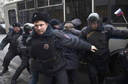 Russian opposition leader Alexei Navalny, in the background, is detained by police officers in Moscow, Russia, Sunday, Jan. 28, 2018. Opposition politician Alexey Navalny calls for nationwide protests following Russia's Central Election Commission's decision to ban his presidential candidacy.