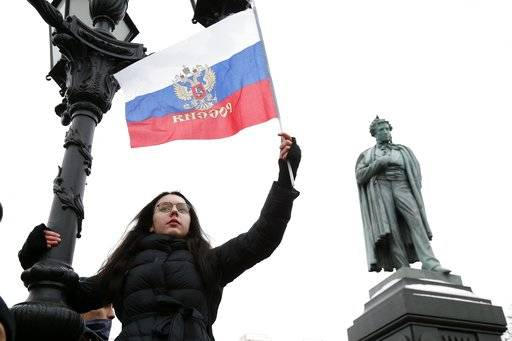 A protester waves a Russian flag during a rally in Moscow, Sunday, Jan. 28, 2018. Opposition politician Alexey Navalny calls for nationwide protests following Russia's Central Election Commission's decision to ban his presidential candidacy.