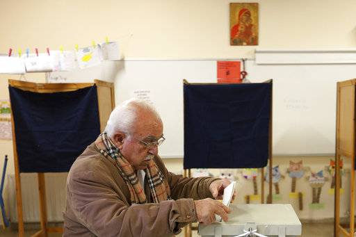 A man votes in presidential election at a polling station in Nicosia, Cyprus Sunday, Jan. 28, 2018. Cypriots are voting for a new president they hope will overcome years of failure to resolve the island-nation's ethnic division and deliver more benefits from an economy on the rebound after a severe financial crisis.