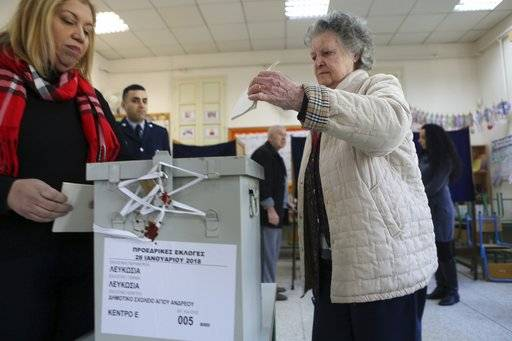 A woman votes during the presidential elections in Nicosia, on Sunday, Jan. 28, 2018. Cypriots are voting for a new president they hope will overcome years of failure to resolve the island-nation's ethnic division and deliver more benefits from an economy on the rebound after a severe financial crisis.