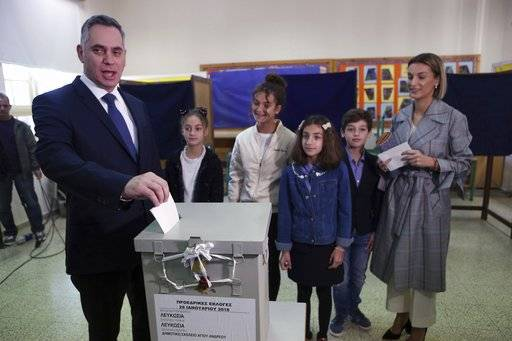 Cypriot Presidential candidate and leader of the center-right DIKO party Nicolas Papadopoulos escorted by his family votes in presidential elections in capital Nicosia, on Sunday, Jan. 28, 2018. Cypriots are voting for a new president they hope will overcome years of failure to resolve the island-nation's ethnic division and deliver more benefits from an economy on the rebound after a severe financial crisis.