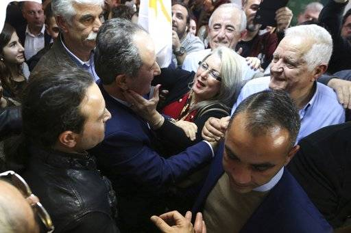 Cypriot Presidential candidate Stavros Malas, center, who ran as an independent with support from the communist-rooted AKEL party, is greeted by his supporters in Nicosia, on Sunday, Jan. 28, 2018. The final tally from Sunday's first round of election showed President Nicos Anastasiades garnering 35.5 percent of the vote as Malas finished second with 30.25 percent.