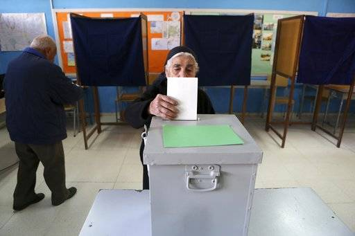 An elderly woman casts her ballot during the presidential elections in Nicosia, on Sunday, Jan. 28, 2018. Cypriots are voting for a new president they hope will overcome years of failure to resolve the island-nation's ethnic division and deliver more benefits from an economy on the rebound after a severe financial crisis.