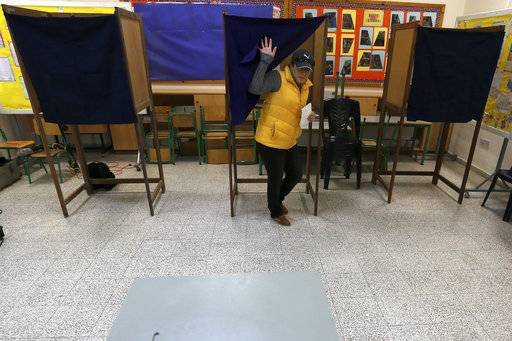 A woman leaves the booth as she votes in presidential elections in Nicosia, Cyprus Sunday, Jan. 28, 2018. Cypriots are voting for a new president they hope will overcome years of failure to resolve the island-nation's ethnic division and deliver more benefits from an economy on the rebound after a severe financial crisis.