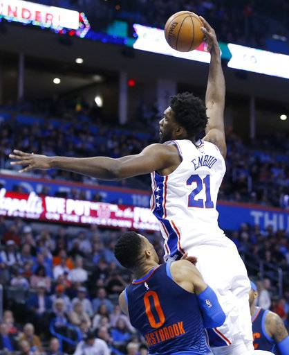 Philadelphia 76ers center Joel Embiid (21) goes up for a dunk in front of Oklahoma City Thunder guard Russell Westbrook (0) in the first half of an NBA basketball game in Oklahoma City, Sunday, Jan. 28, 2018.