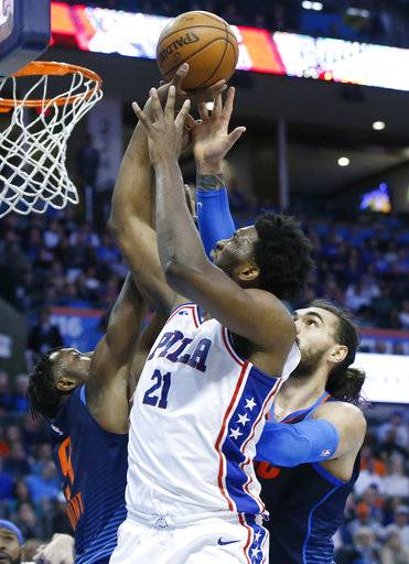 Philadelphia 76ers center Joel Embiid (21) shoots between Oklahoma City Thunder forward Jerami Grant, left, and center Steven Adams, right, in the first half of an NBA basketball game in Oklahoma City, Sunday, Jan. 28, 2018.
