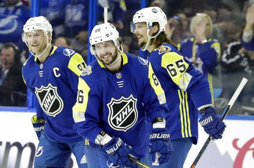 Atlantic Division's Nikita Kucherov, center, of the Tampa Bay Lightning, smiles as he is congratulated by Steven Stamkos, left, of the Tampa Bay Lightning, and Erik Karlsson, right, of the Ottawa Senators, after scoring a hat trick during the NHL hockey All-Star game with the Metropolitan Division Sunday, Jan. 28, 2018 in Tampa, Fla.