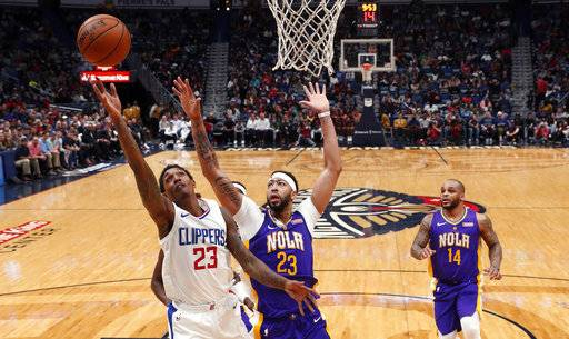 Los Angeles Clippers guard Lou Williams (23) goes to the basket against New Orleans Pelicans forward Anthony Davis (23) in the second half of an NBA basketball game in New Orleans, Sunday, Jan. 28, 2018. The Clippers won 112-103.