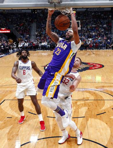 New Orleans Pelicans guard Ian Clark (2)3 slam dunks over Los Angeles Clippers forward Blake Griffin (32) and center DeAndre Jordan (6) in the first half of an NBA basketball game in New Orleans, Sunday, Jan. 28, 2018.