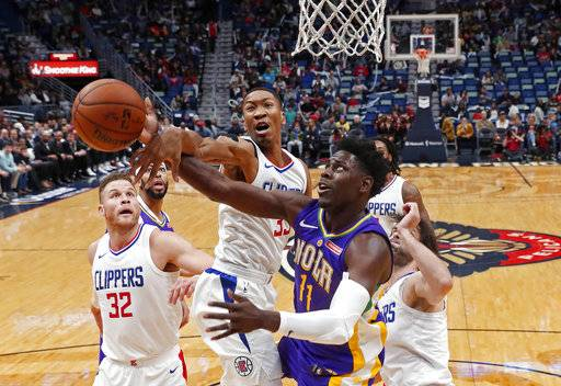 Los Angeles Clippers forward Wesley Johnson (33) blocks a shot by New Orleans Pelicans guard Jrue Holiday (11) in the first half of an NBA basketball game in New Orleans, Sunday, Jan. 28, 2018.