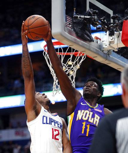 New Orleans Pelicans guard Jrue Holiday (11) blocks a shot by Los Angeles Clippers guard Tyrone Wallace (12) in the first half of an NBA basketball game in New Orleans, Sunday, Jan. 28, 2018.
