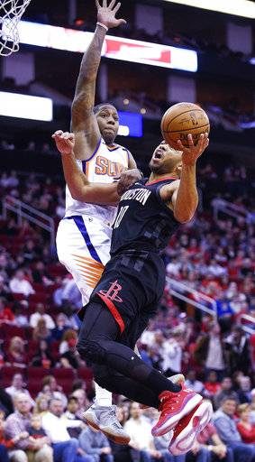 Houston Rockets guard Eric Gordon, right, drives to the basket as Phoenix Suns guard Isaiah Canaan defends during the first half of an NBA basketball game, Sunday, Jan. 28, 2018, in Houston.