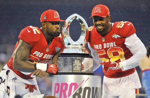 AFC linebacker Von Miller (58), of the Denver Broncos and tight end Delanie Walker (82), of the Tennessee Titans, pose with the NFL Pro Bowl trophy after defeating the AFC 24-23, in Orlando, Fla., Sunday, Jan. 28, 2018.