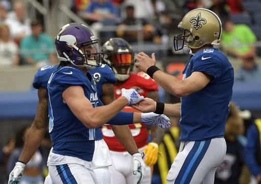 NFC quarterback Drew Brees (9), of the New Orleans Saints, celebrates after wide receiver Adam Thielen (19), of the Minnesota Vikings, scored a touchdown, during the first half of the NFL Pro Bowl football game, Sunday, Jan. 28, 2018, in Orlando, Fla.