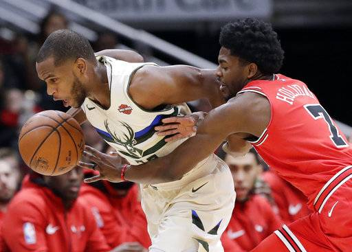 Milwaukee Bucks forward Khris Middleton, left, drives against Chicago Bulls guard Justin Holiday during the first half of an NBA basketball game Sunday, Jan. 28, 2018, in Chicago.