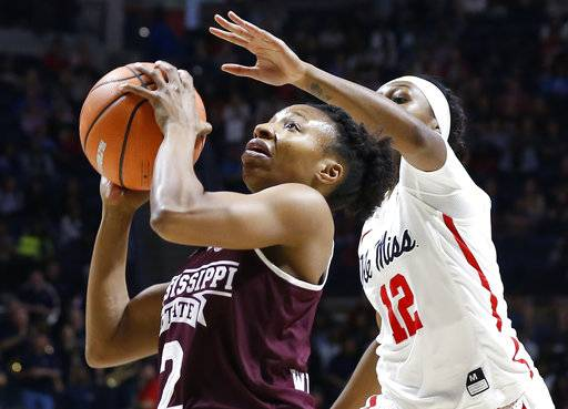 Mississippi guard Barbara Johnson (12) reaches over the top to block a shot by Mississippi State guard Morgan William (2) during the first half of the NCAA college basketball game in Oxford, Miss., Sunday, Jan. 28, 2018. Mississippi State won 69-49.