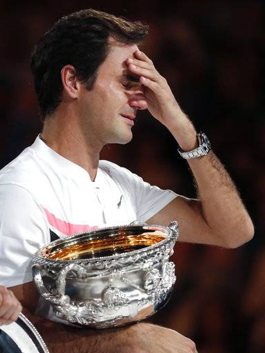 Switzerland's Roger Federer wipes tears from his eyes as he holds his trophy after defeating Croatia's Marin Cilic during the men's singles final at the Australian Open tennis championships in Melbourne, Australia, Sunday, Jan. 28, 2018.