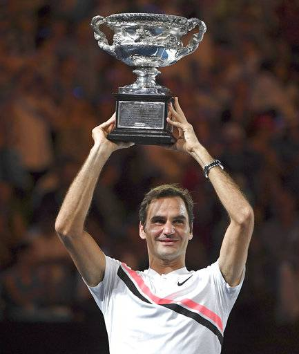 Switzerland's Roger Federer holds his trophy aloft after defeating Croatia's Marin Cilic during the men's singles final at the Australian Open tennis championships in Melbourne, Australia, Sunday, Jan. 28, 2018.