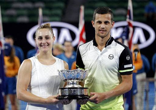 Canada's Gabriela Dabrowski, left, and Croatia's Mate Pavic hold their trophy aloft after defeating Hungary's Timea Babos and partner India's Rohan Bopanna in the mixed doubles final at the Australian Open tennis championships in Melbourne, Australia, Sunday, Jan. 28, 2018.