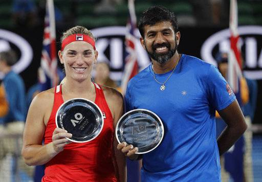 Hungary's Timea Babos, left, and partner India's Rohan Bopanna hold their runner-up trophies after losing to Canada's Gabriela Dabrowski and Croatia's Mate Pavic in the mixed doubles final at the Australian Open tennis championships in Melbourne, Australia, Sunday, Jan. 28, 2018.