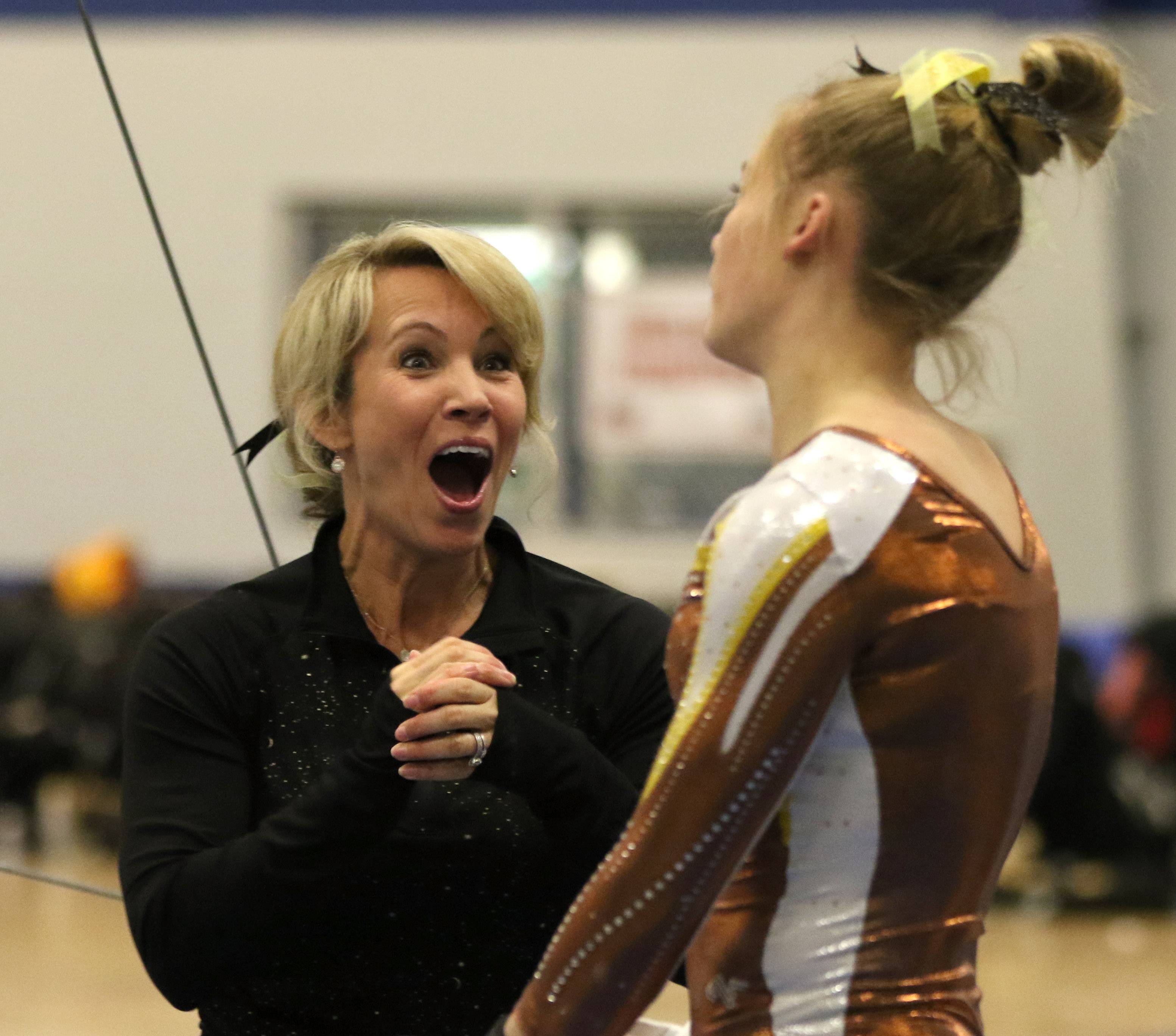 Carmel's Kyla Rapplean is greeted by coach Sarah Mikrut Doyle after an uneven parallel bars performance during regional gymnastics action at Wheeling on Monday evening.