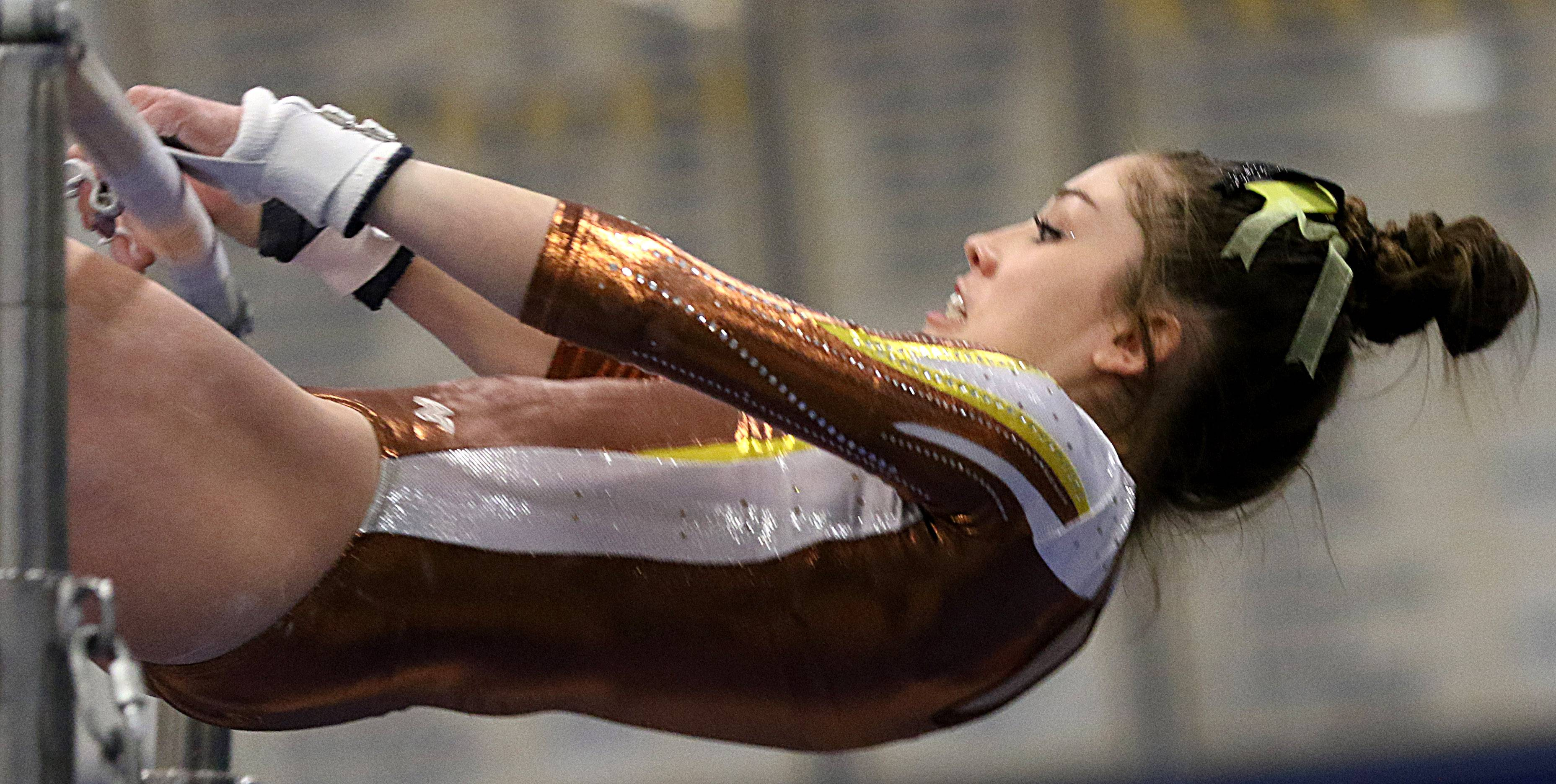 Carmel's Audrey Legarreta performs on the uneven parallel bars during regional gymnastics action at Wheeling on Monday evening.