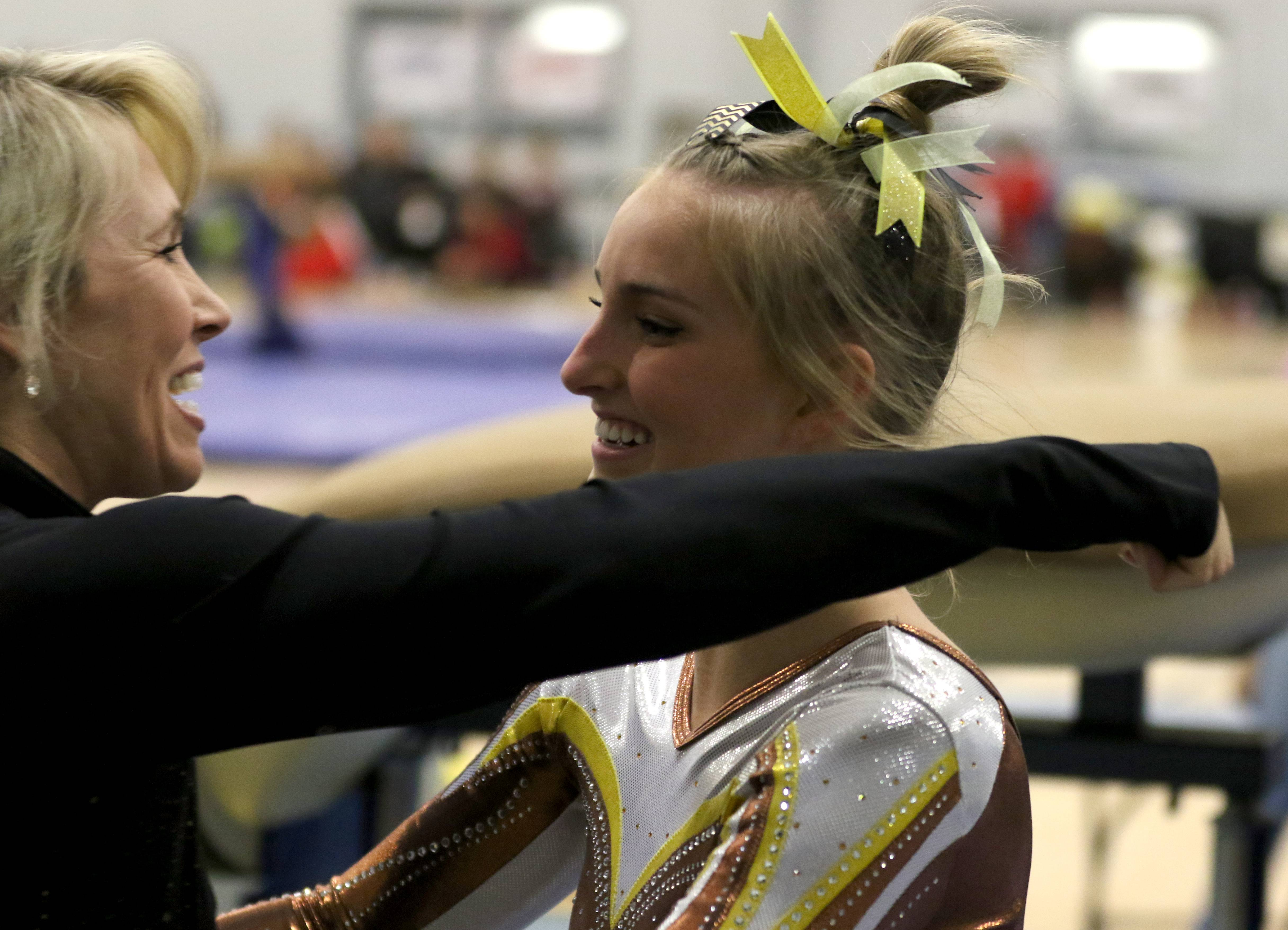 Carmel's Kelly Gustafson, right, is greeted by coach Sarah Mikrut Doyle following Gustafson's vault during regional gymnastics action at Wheeling on Monday evening.