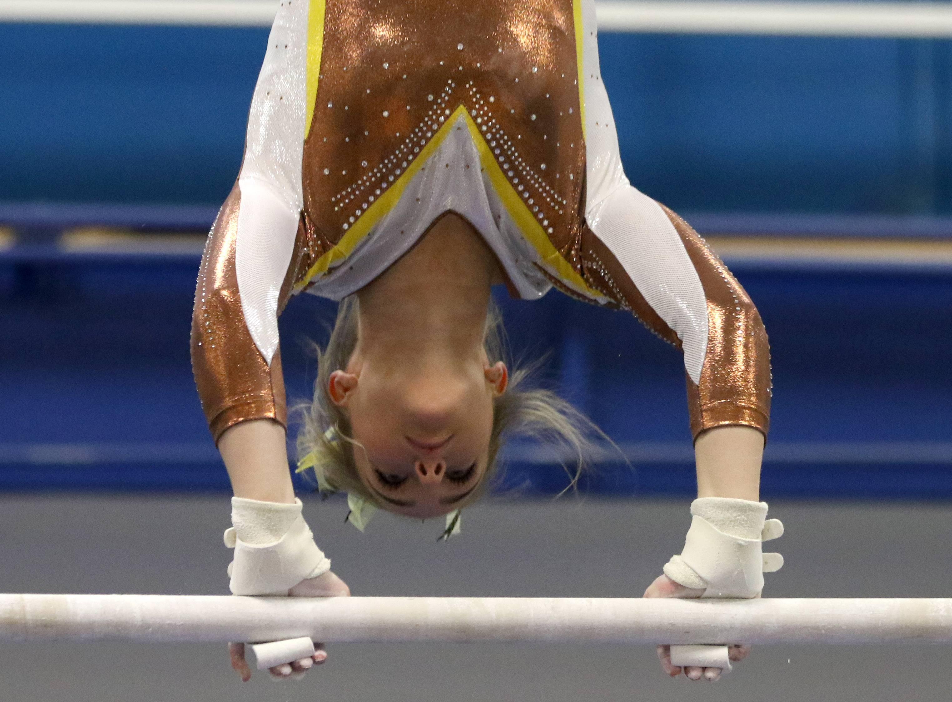 Carmel's Kelly Gustafson performs on the uneven parallel bars during regional gymnastics action at Wheeling on Monday evening.