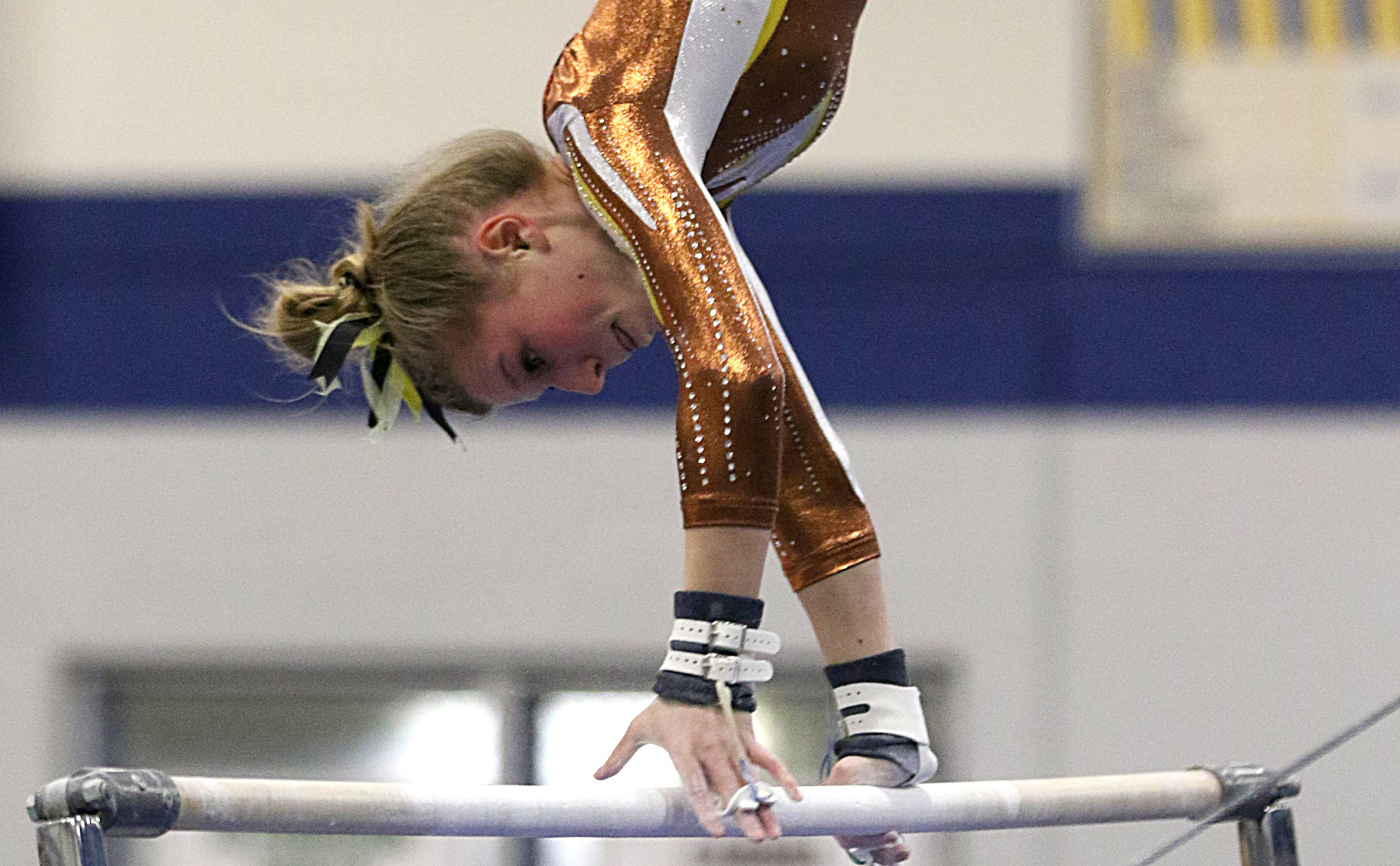 Carmel's Lyndsey Basara performs on the uneven parallel bars during regional gymnastics action at Wheeling on Monday evening.