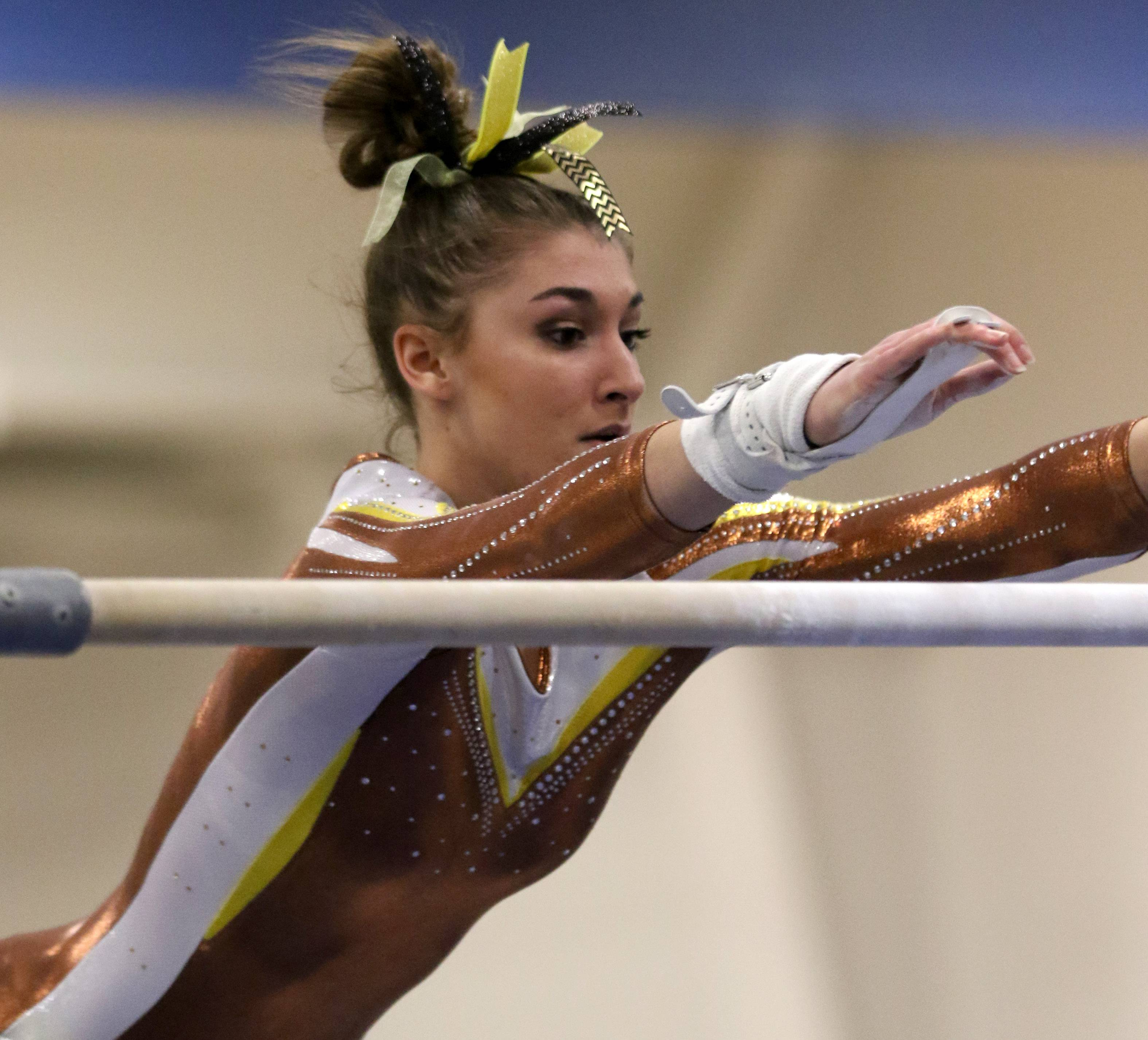 Carmel's Isabella Kropiwiec performs on the uneven parallel bars during regional gymnastics action at Wheeling on Monday evening.