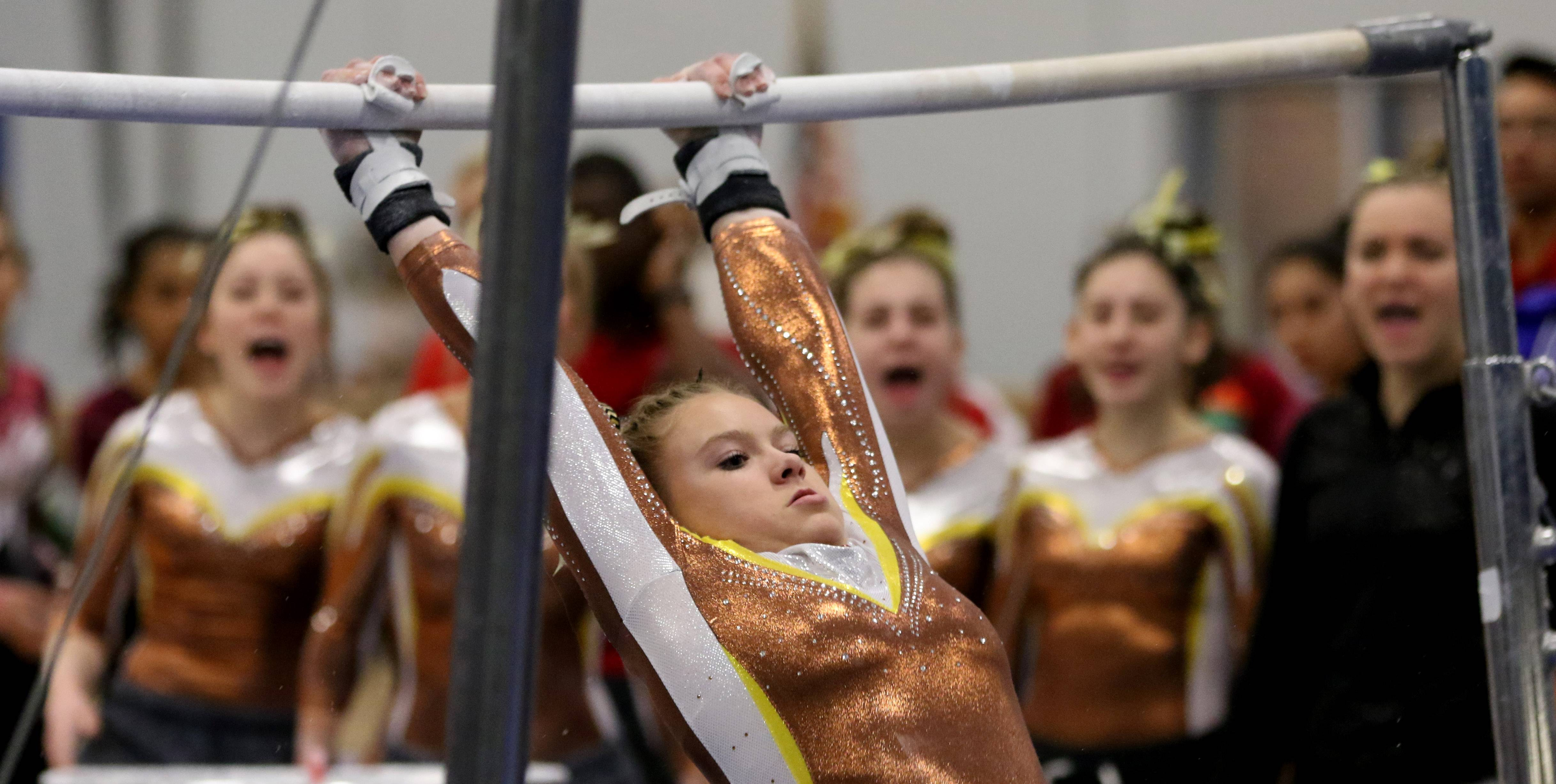 Carmel's Kyla Rapplean is cheered by teammates as she performs on the uneven parallel bars during regional gymnastics action at Wheeling on Monday evening.