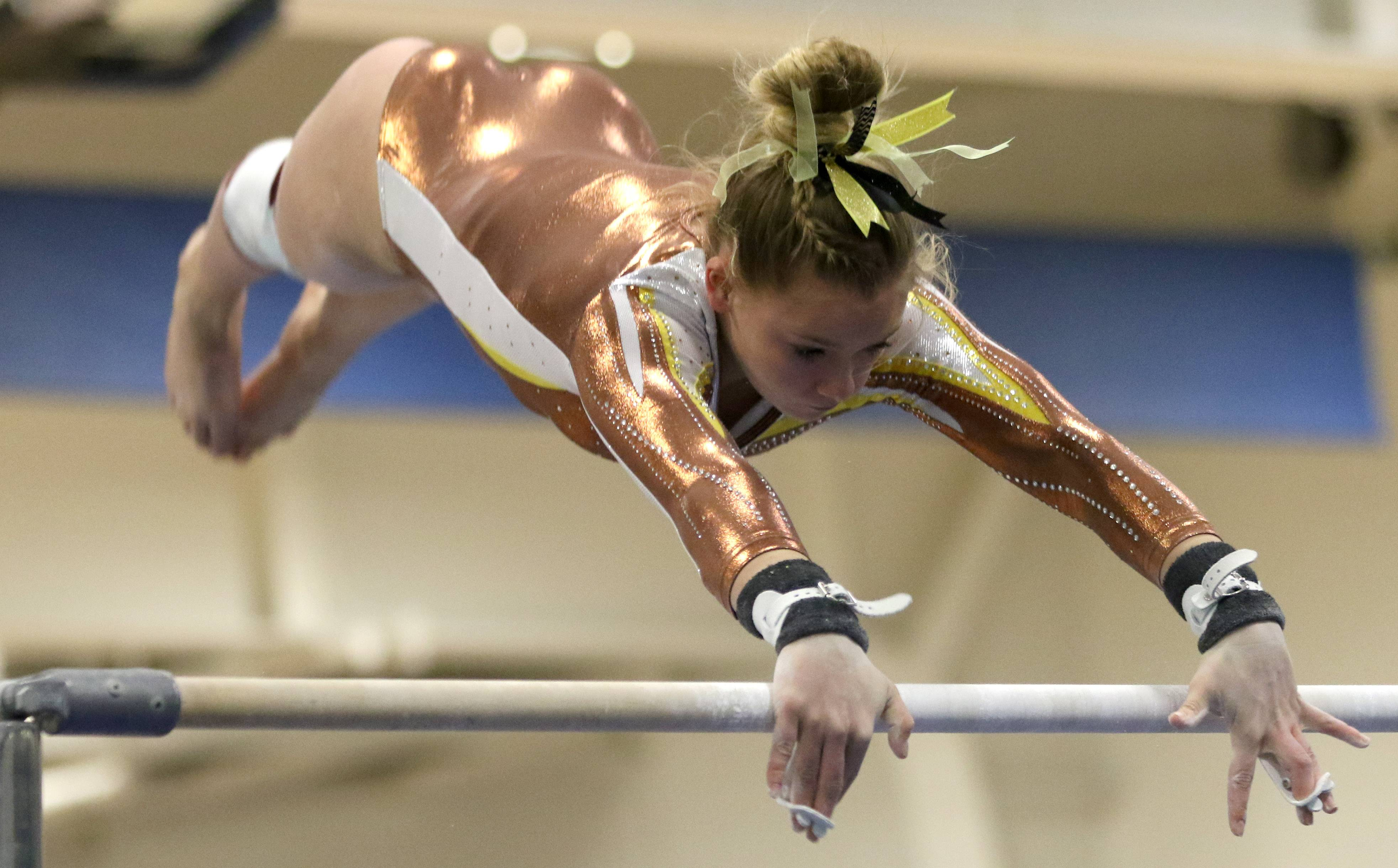 Carmel's Kyla Rapplean performs on the uneven parallel bars during regional gymnastics action at Wheeling on Monday evening.