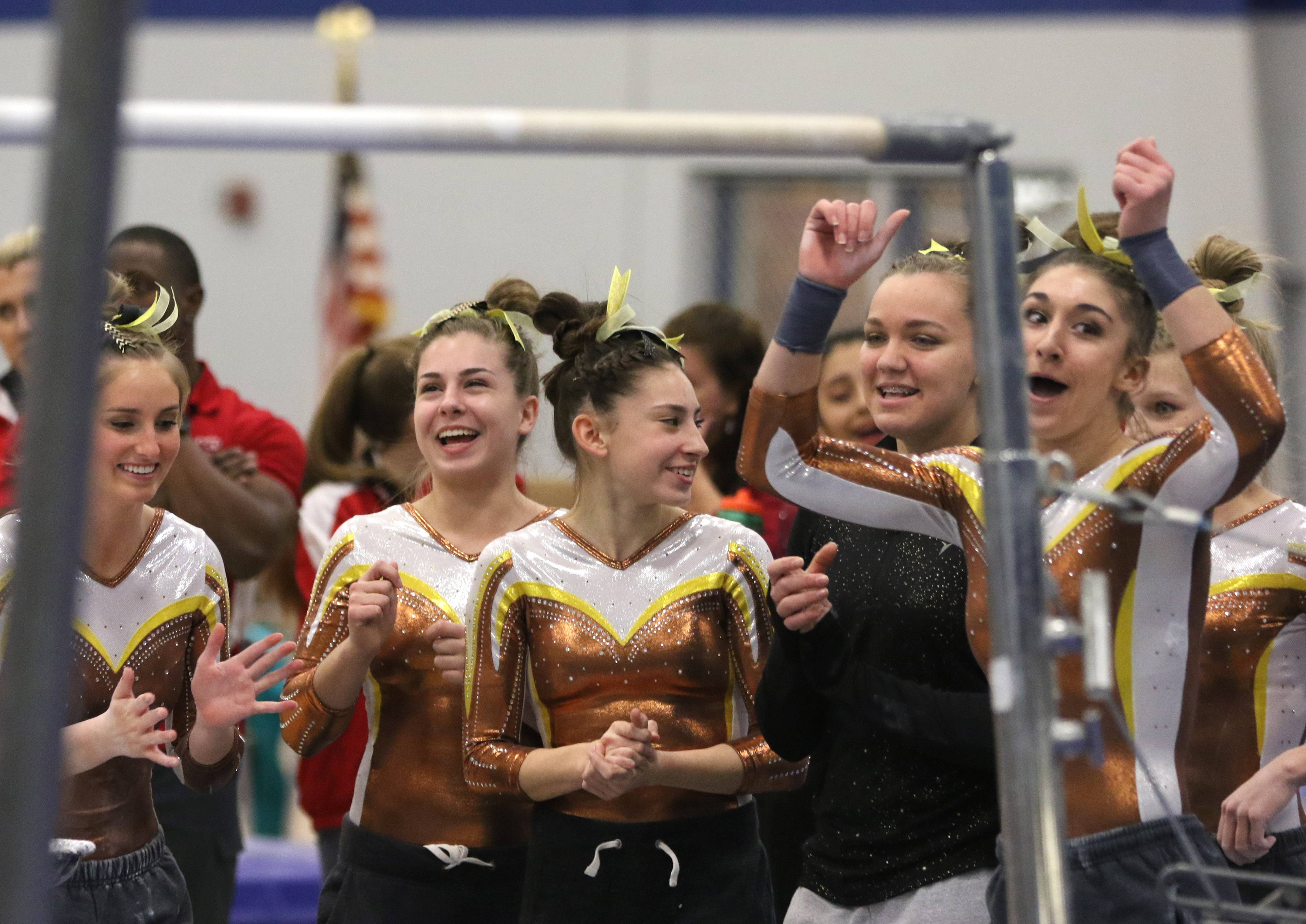 Carmel gymnasts cheer as teammate Kyla Rapplean performs on the uneven parallel bars during regional action at Wheeling on Monday evening.