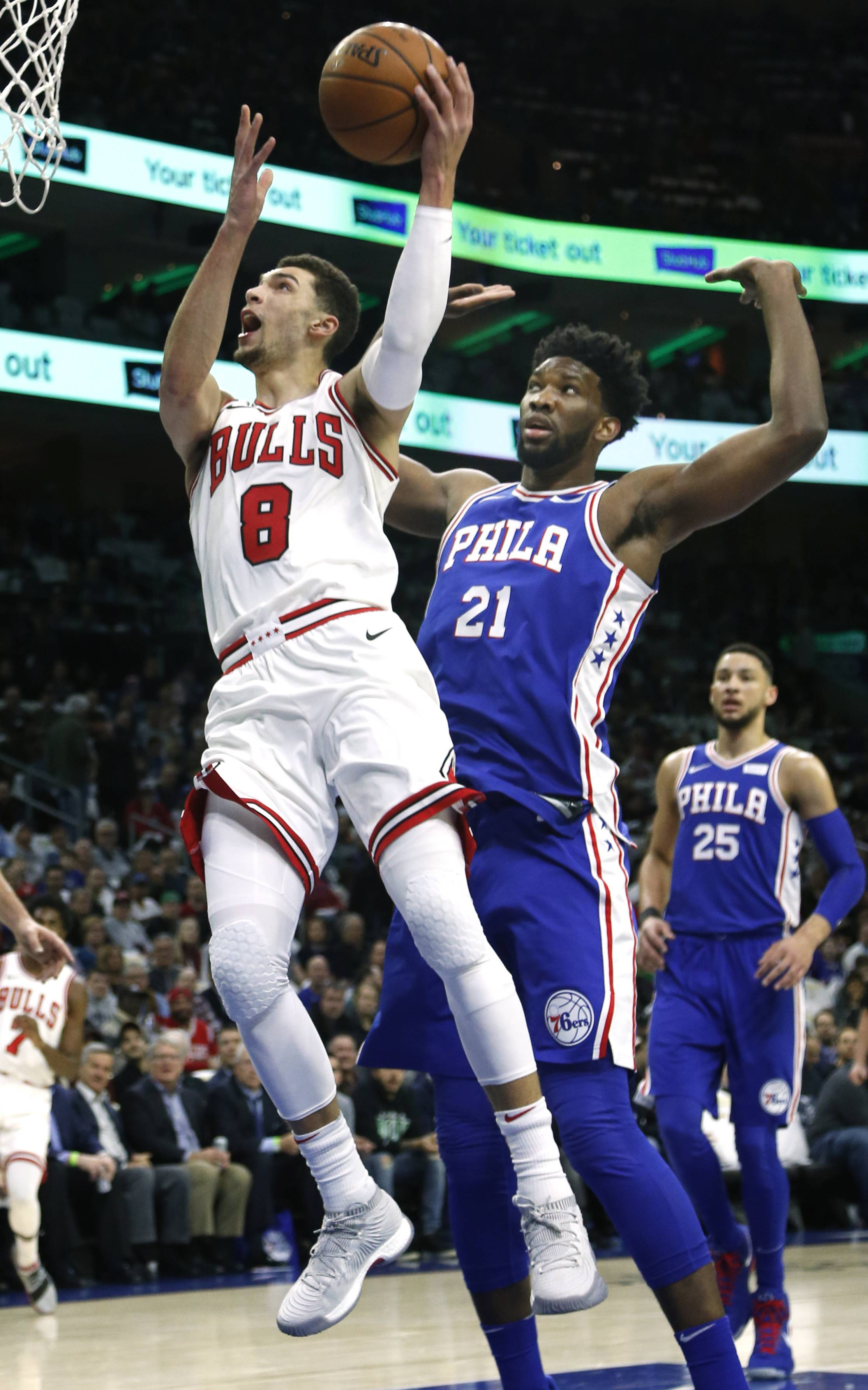 Chicago Bulls guard Zach LaVine (8) goes to the basket past Philadelphia 76ers center Joel Embiid (21) during the first half on an NBA basketball game, Wednesday, Jan. 24, 2018, in Philadelphia.