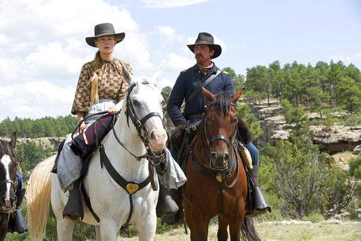 "FILE - This undated image released by Entertainment Studios Motion Pictures shows Rosamund Pike, left, and Christian Bale in a scene from ""Hostiles."" ""Maze Runner: The Death Cure� is the highest grossing film of the weekend, but according to studio estimates Sunday, Jan. 28, 2018. In third place, the Christian Bale-led Western ""Hostiles�. (Entertainment Studios Motion Pictures via AP, File)"