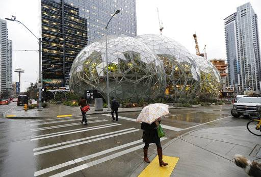 Pedestrians walk past the Amazon Spheres in downtown Seattle on the day of the grand opening of the geodesic domes, which will primarily serve as a working and gathering space for Amazon.com employees, Monday, Jan. 29, 2018, in Seattle.